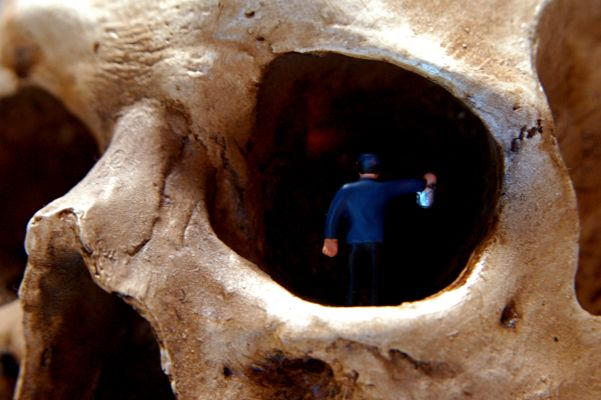 A small figure of a person walks into the eye socket of a skull, holding a lantern.