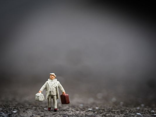 Photograph of a miniature person walking while carrying bags.