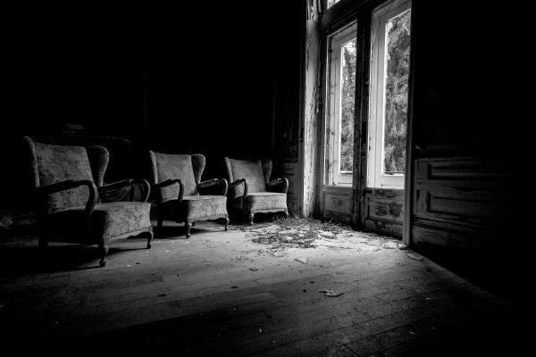 Three empty chairs in an abandoned building face an open window.