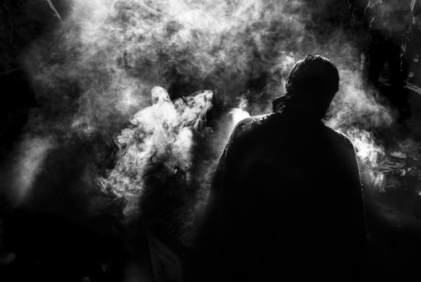 Silhouette of a person surrounded by white smoke.